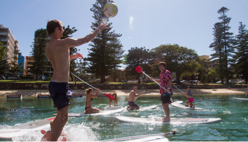 People playing Stand Up Paddle Boarding in Manly